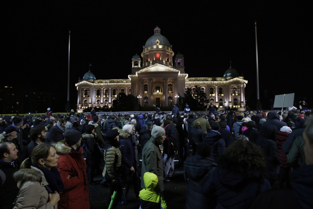 People march during a protest in front of the Serbian Parliament building in Belgrade, Serbia, Saturday, Dec. 8, 2018. Thousands of people are marchin