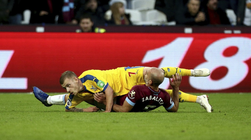 Crystal Palace's Max Meyer, top, and West Ham United's Pablo Zabaleta collide during their English Premier League soccer match at The London Stadium,