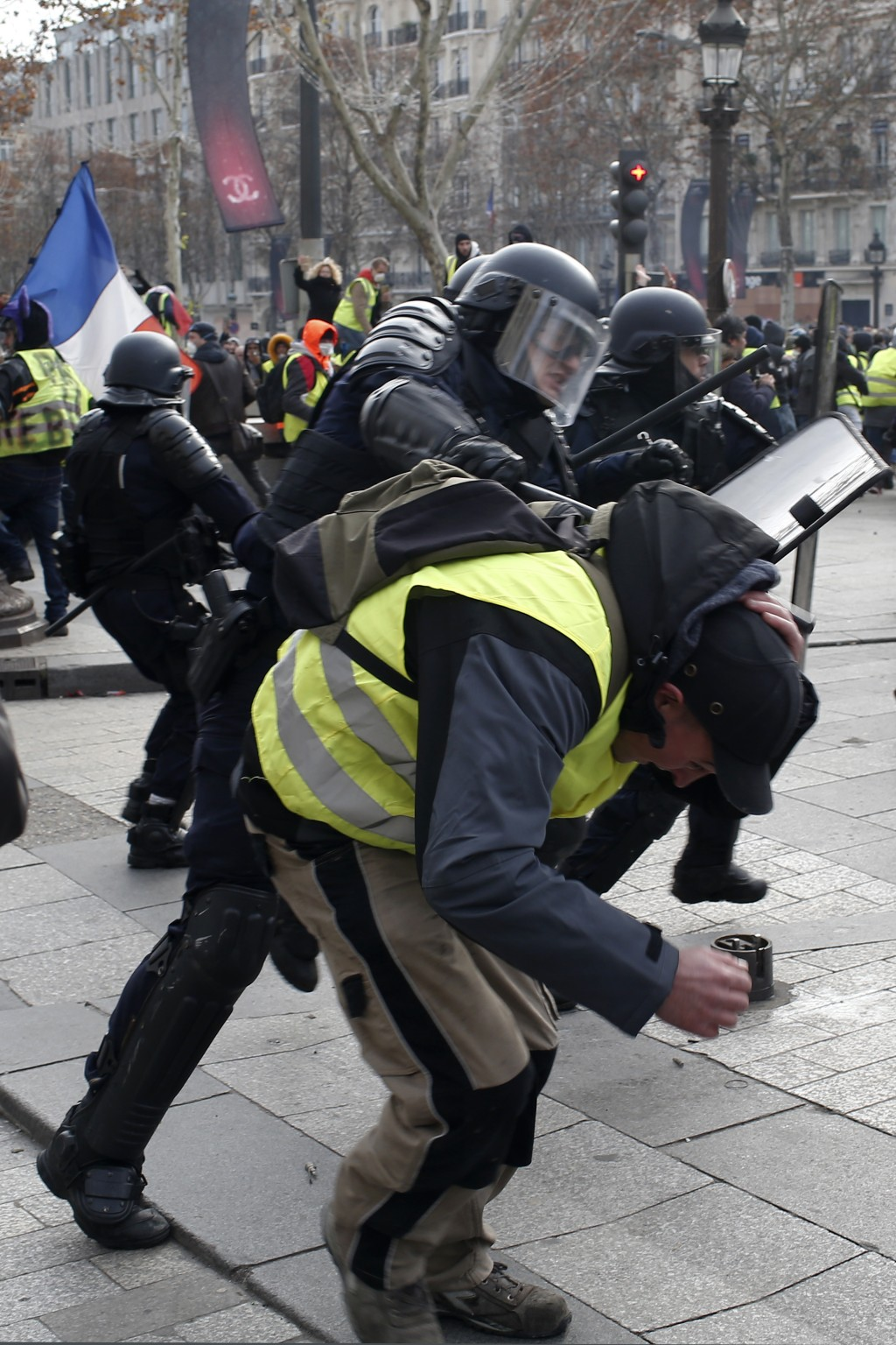 A riot police officer beats a demonstrator on the Champs-Elysees avenue Saturday, Dec. 8, 2018 in Paris. Crowds of yellow-vested protesters angry at P