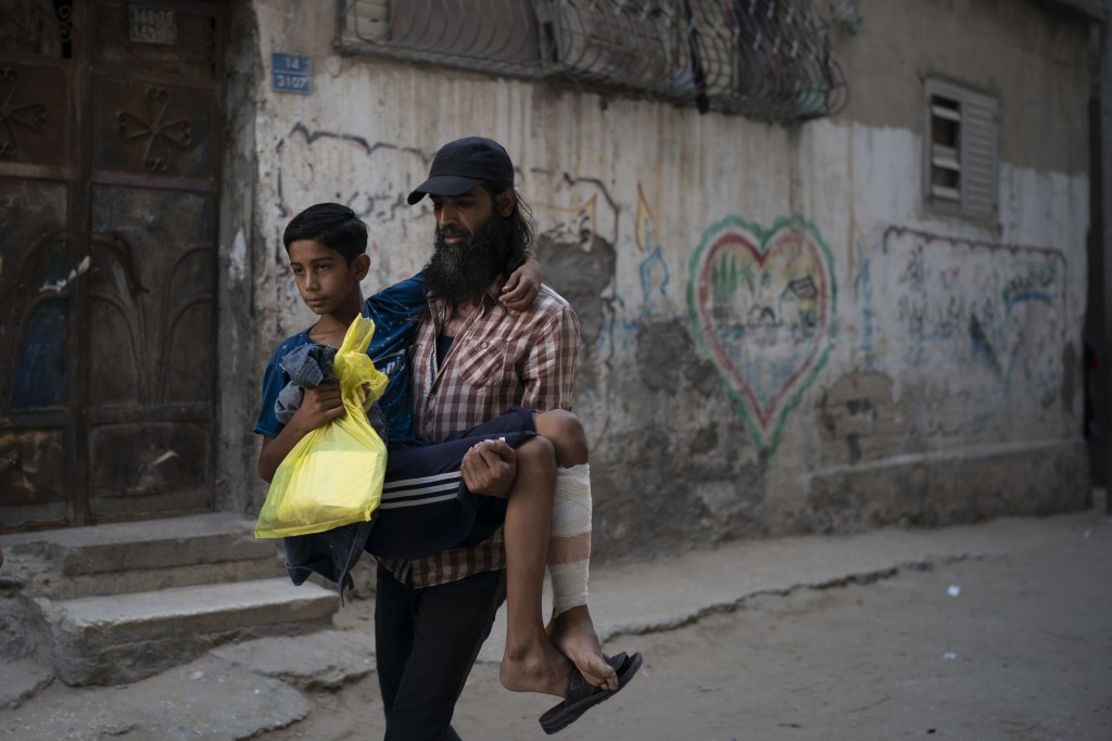 In this Sept. 16, 2018, photo, Raed Abu Khader, right, carries his 12-year-old son Mohammed as they return from the hospital in Gaza City. Mohammed wa...