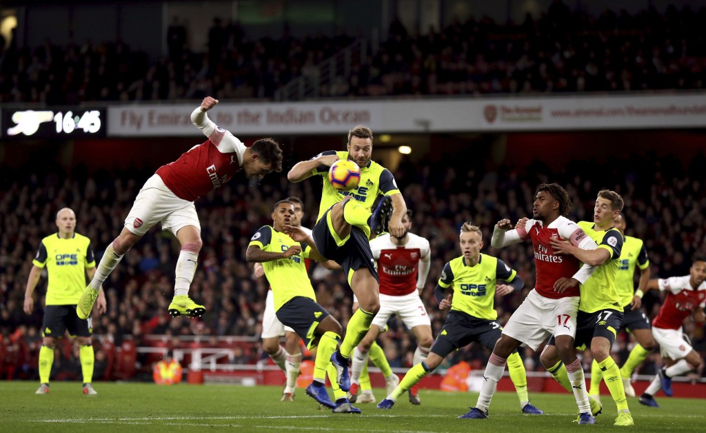 Arsenal's Lucas Torreira, left, heads the ball towards goal, during the English Premier League soccer match between Arsenal and Huddersfield, at the E