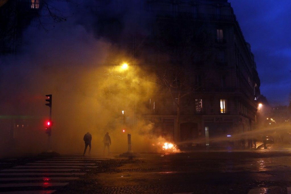 Demonstrators walk away from a cloud of tear gas fired by the police during an anti-government protest, in Paris, France, Saturday, Dec. 8, 2018. Crow