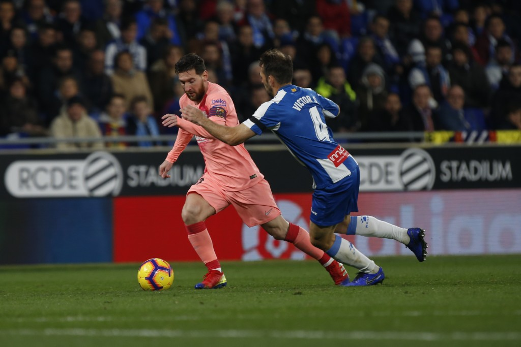 FC Barcelona's Lionel Messi, left, kicks the ball during the Spanish La Liga soccer match between Espanyol and FC Barcelona at RCDE stadium in Cornell