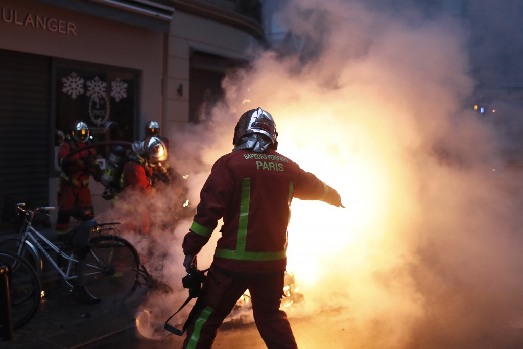 Firefighters try to extinguished a car set on fire by demonstrators during clashes with riot police, in Paris, France, Saturday, Dec. 8, 2018. Crowds