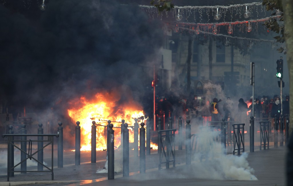 Demonstrators stand behind a burning car during clashes, Saturday, Dec. 8, 2018 in Marseille, southern France. French riot police fired tear gas and w