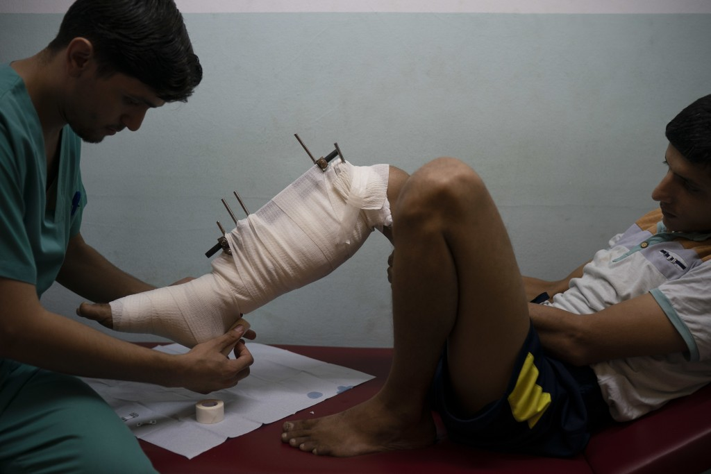 In this Sept. 10, 2018, photo, Mahmoud Abu Assi, who was shot in the leg during a demonstration, has his bandage changed in a clinic run by MSF (Docto...