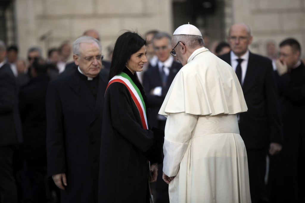 Pope Francis greets Rome's Mayor Virginia Raggi after praying in front of the statue of the Virgin Mary, near Rome's Spanish Steps, Saturday, Dec. 8,