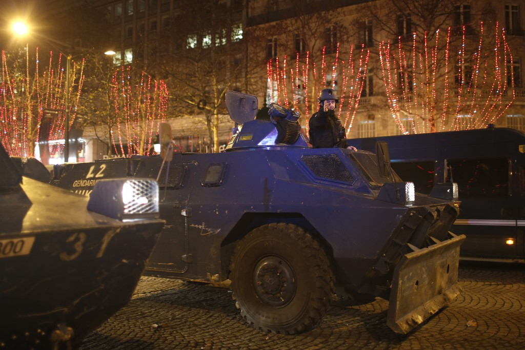 An armored military vehicle drives down the Champs-Elysees avenue after clashes Saturday, Dec. 8, 2018 in Paris. Crowds of yellow-vested protesters an