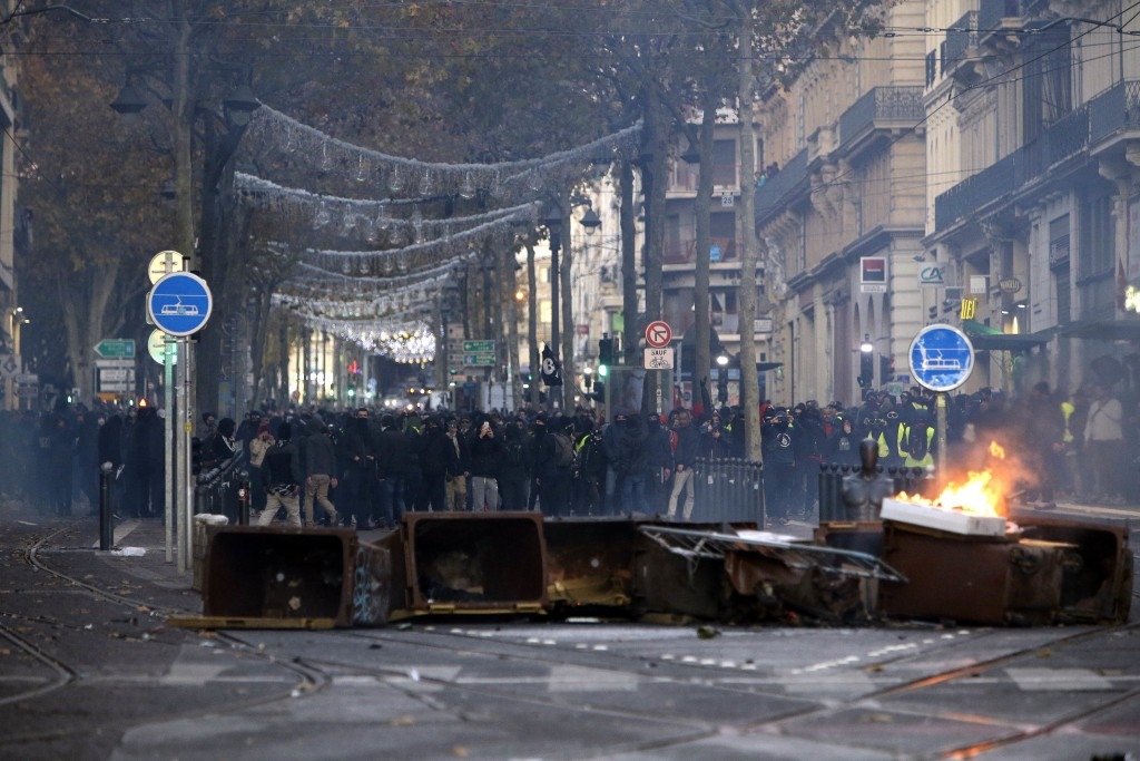 Demonstrators stand behind a burning bin during clashes, Saturday, Dec. 8, 2018 in Marseille, southern France. The rumble of armored police trucks and...