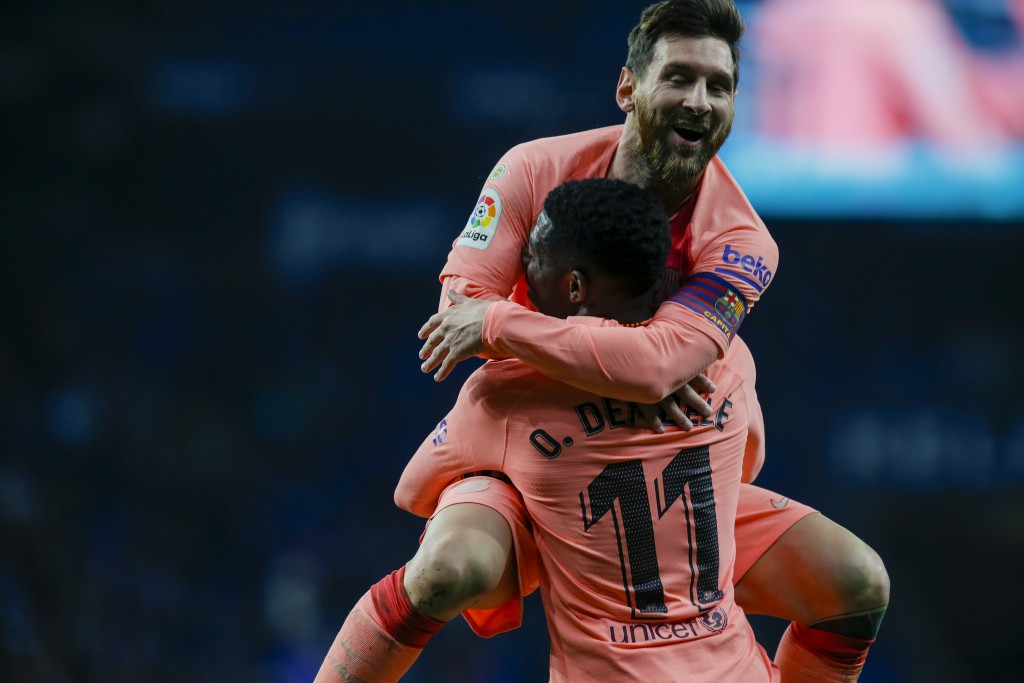 FC Barcelona's Lionel Messi celebrates with teammate Ousmane Dembele during the Spanish La Liga soccer match between Espanyol and FC Barcelona at RCDE