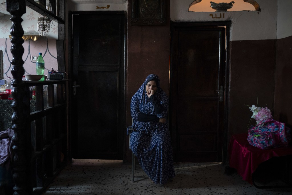 In this Sept. 12, 2018, photo, Amani al-Bilbisi, sits outside her son Mohammed Khader's room as he lays in bed in Gaza City. Mohammed was shot in the ...