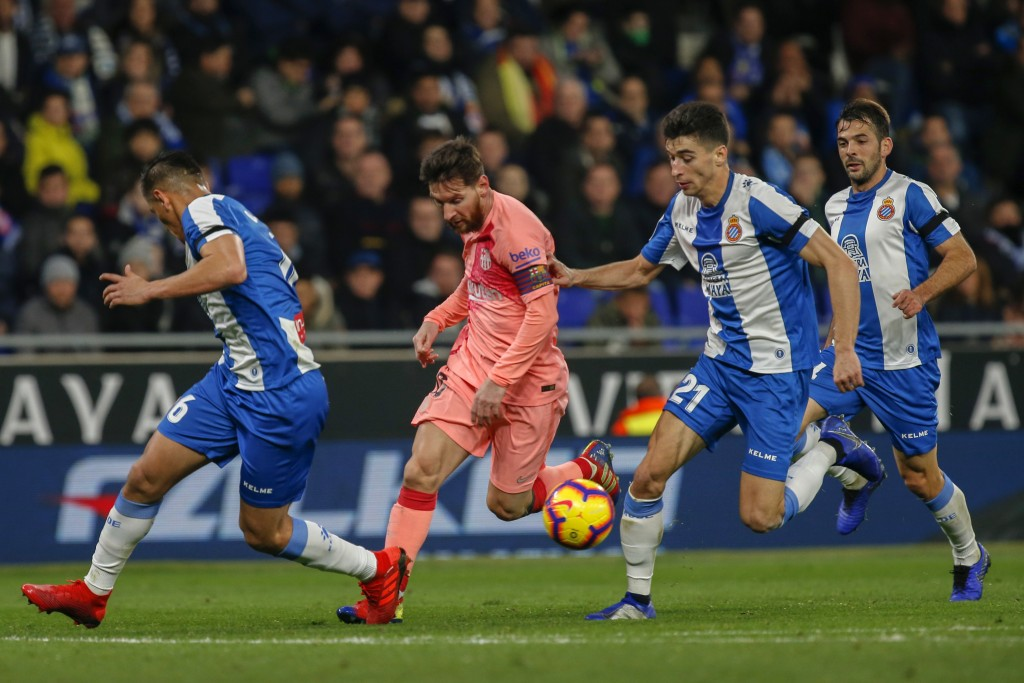 FC Barcelona's Lionel Messi, center, controls the ball during the Spanish La Liga soccer match between Espanyol and FC Barcelona at RCDE stadium in Co