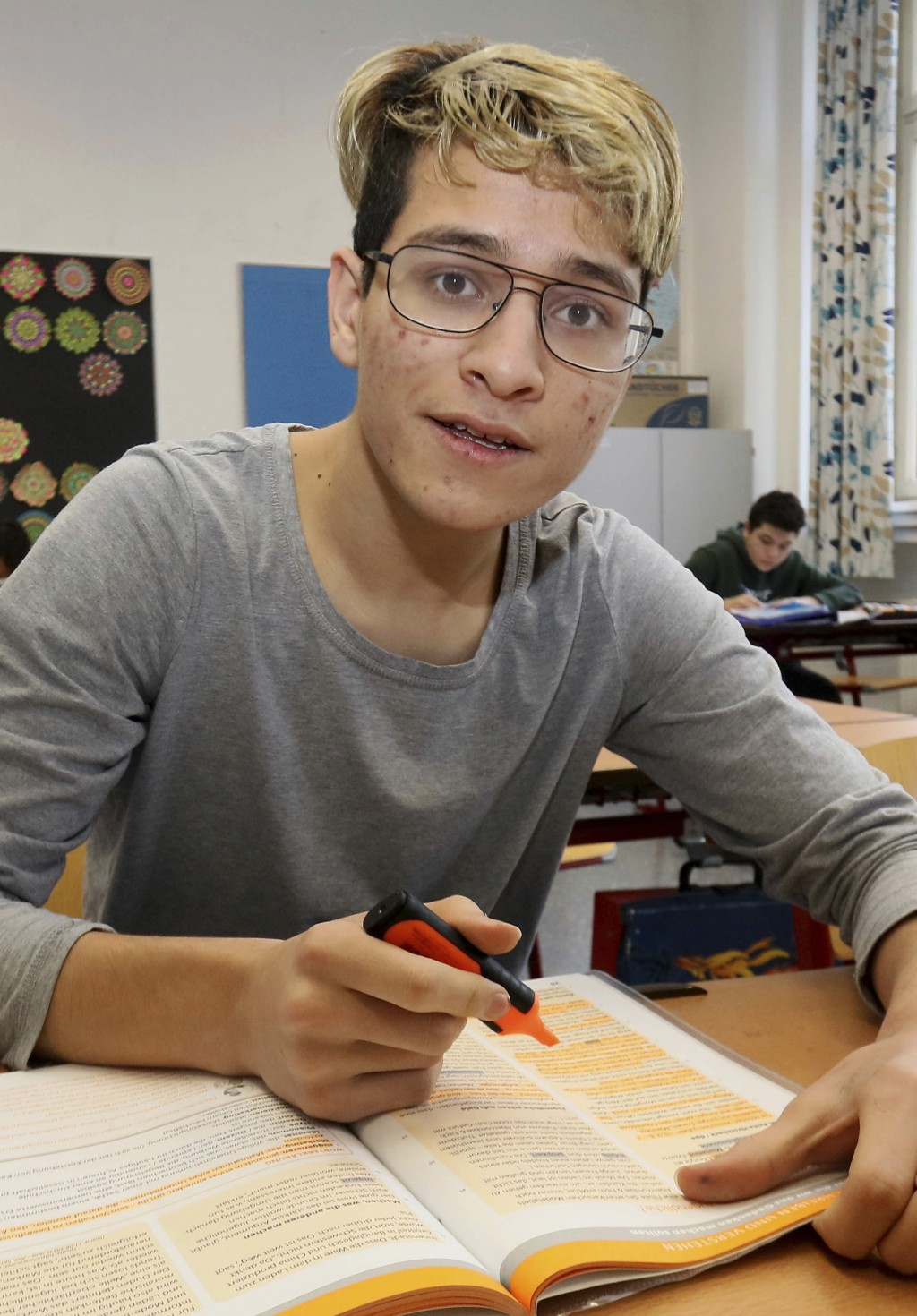In this Dec. 7, 2018 photo Hassan Husseini from Afghanistan poses for a photograph as he attends a class in a school in Vienna, Austria. Like the near...