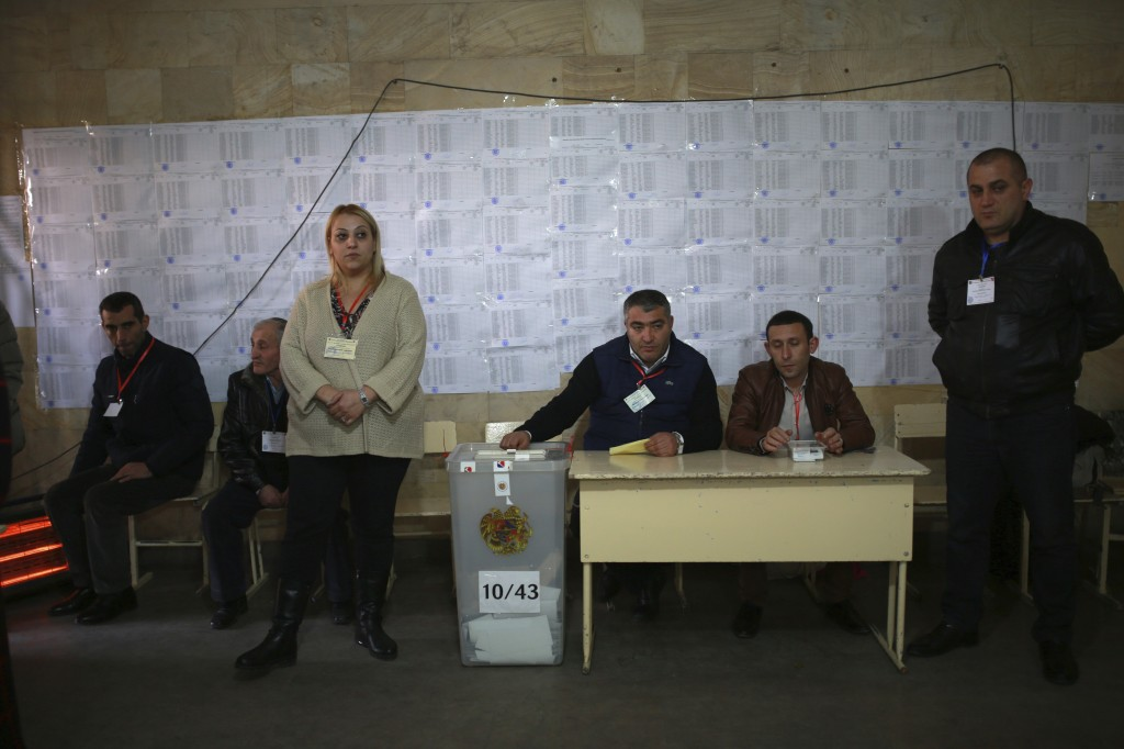 Election officials wait for voters in a polling station during an early parliamentary election in Yerevan, Armenia, Sunday, Dec. 9, 2018. The charisma