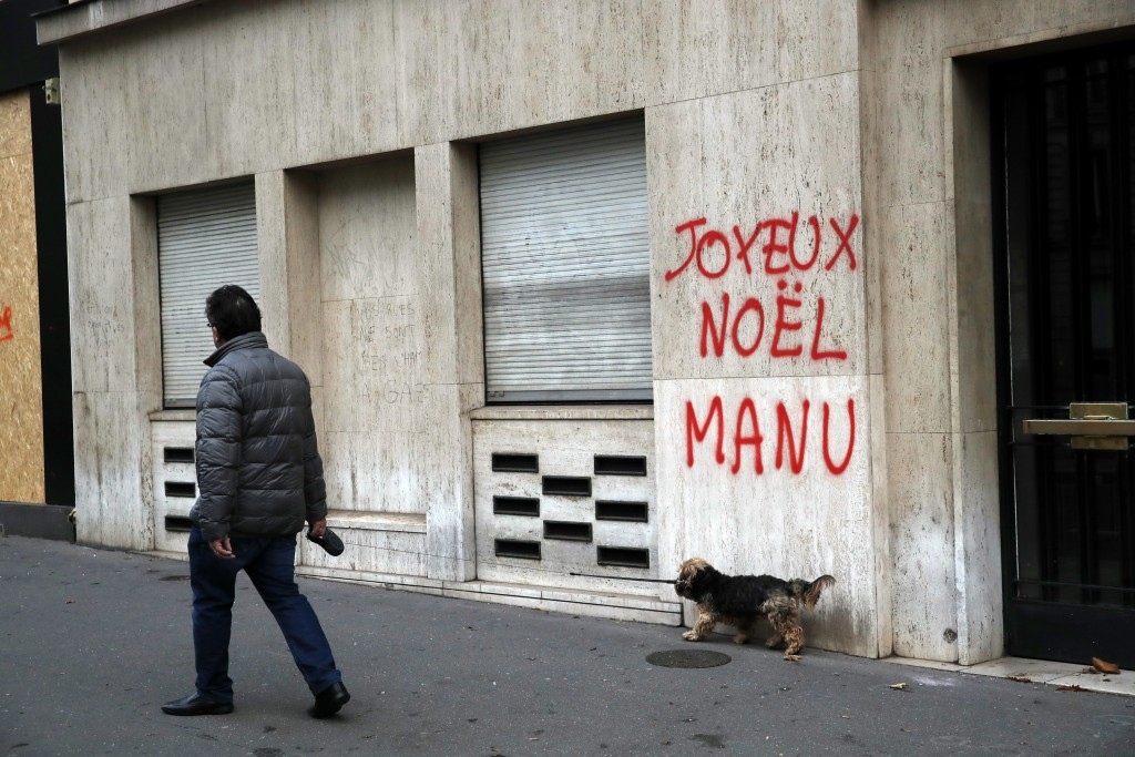 A man walks his dog past a tag reading : Happy Christmas Manu, referring to French President Emmanuel Macron, in Paris, Sunday, Dec. 9, 2018. Paris mo...