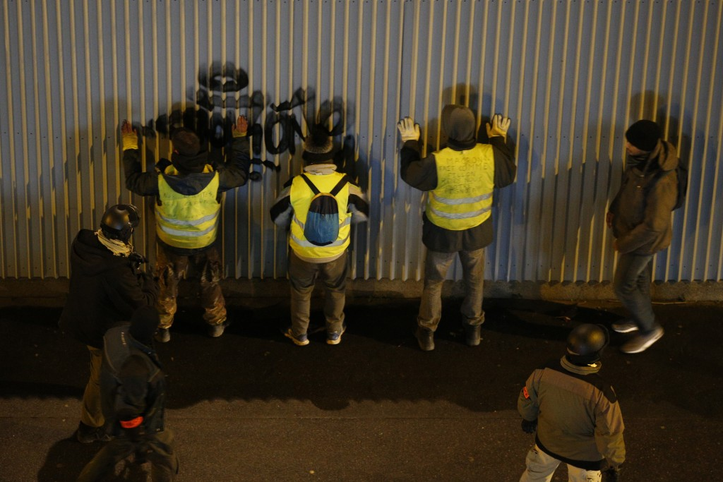 Plainclothes police officers search yellow-vested protesters during an anti-government protest, in Paris, France, Saturday, Dec. 8, 2018. Crowds of pr