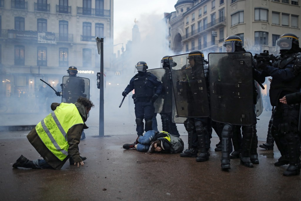 Police officers clash with demonstrators in Lyon, central France, Saturday, Dec. 8, 2018. The grassroots movement began as resistance against a rise i