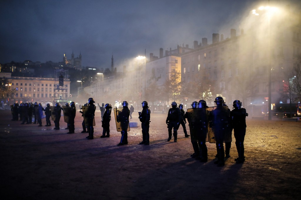 Police officers face demonstrators in Lyon, central France, Saturday, Dec. 8, 2018. The grassroots movement began as resistance against a rise in taxe