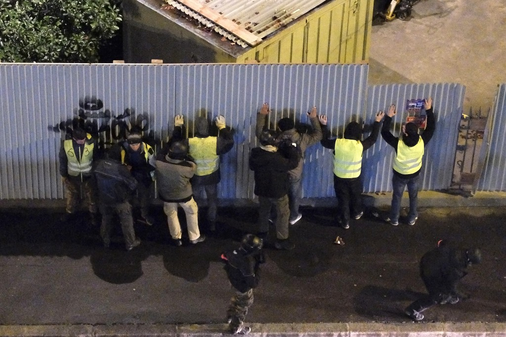 Demonstrators are being checked by police officers Saturday, Dec. 8, 2018 in Paris. Crowds of yellow-vested protesters angry at President Emmanuel Mac