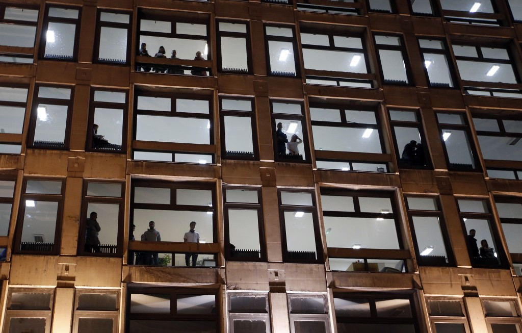 People stand in a building watching a protest in Belgrade, Serbia, Saturday, Dec. 8, 2018. Thousands of people are marched  in Serbia against the auto