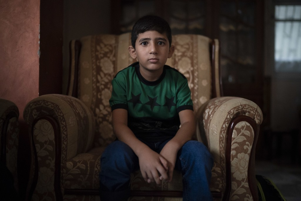 In this Sept. 17, 2018, photo, 8-year-old Mohamed al-Dalo sits in his living room as he waits for breakfast before going to school in Gaza City. Ever ...