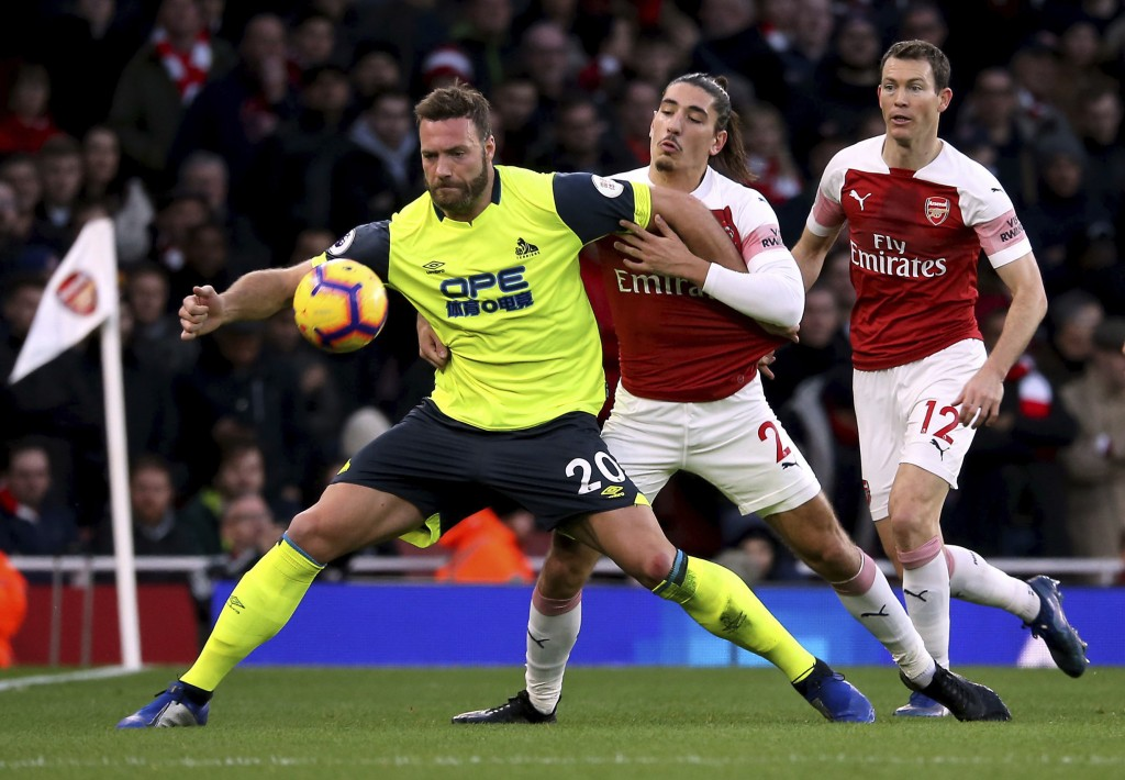 Huddersfield Town's Laurent Depoitre, left, and Arsenal's Hector Bellerin battle for the ball during their English Premier League soccer match at the