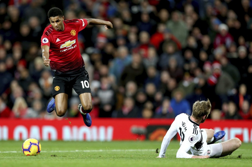 Manchester United's Marcus Rashford, left, jumps over a challenge from Fulham's Tim Ream, right, during the English Premier League soccer match betwee