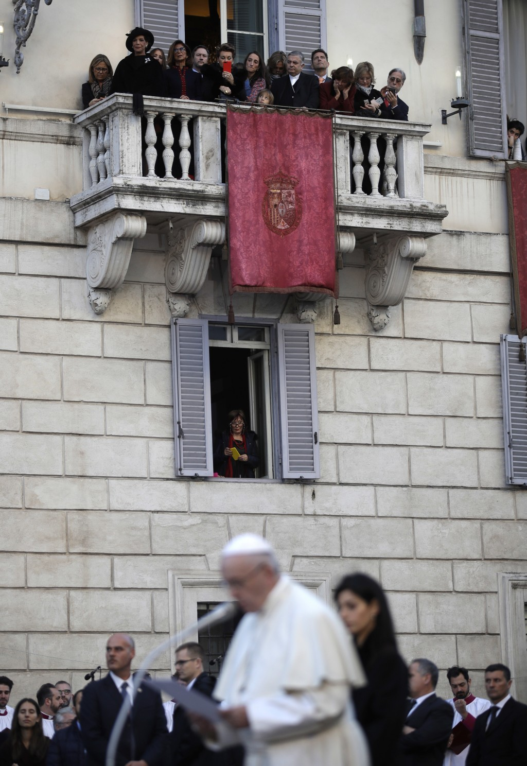People watch from a balcony as Pope Francis delivers his blessing in front of the statue of the Virgin Mary, near Rome's Spanish Steps Saturday, Dec.