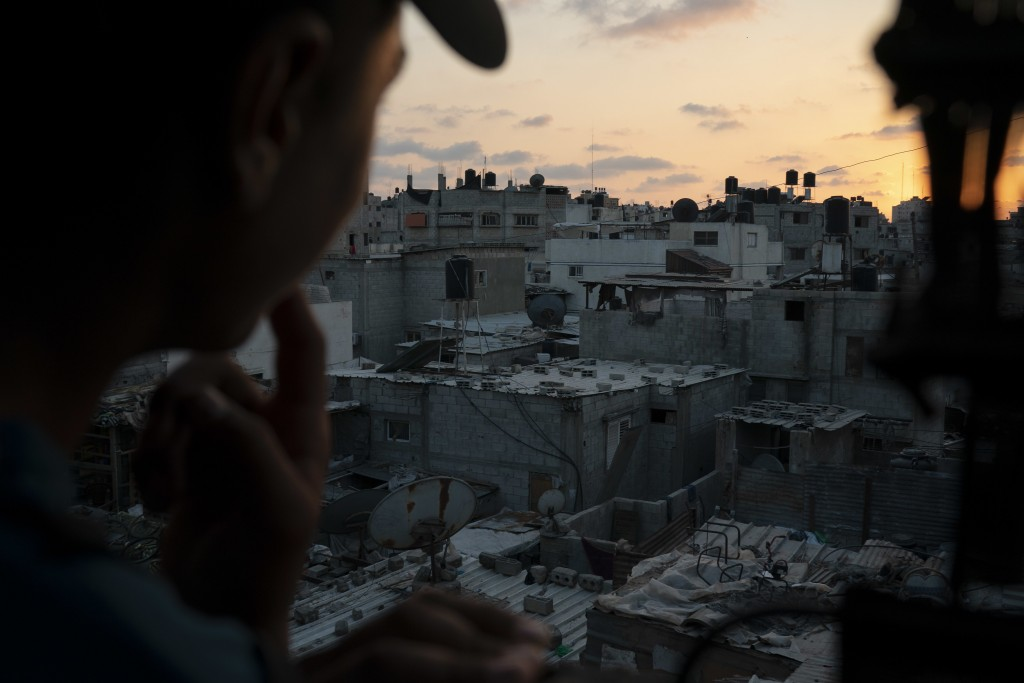 In this Sept. 12, 2018, photo, a boy looks out of the window as the sun sets in Gaza City. Ever since Hamas launched demonstrations in March against I...
