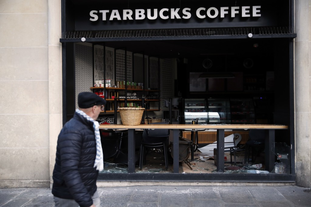 A man walks near a coffee shop whose windows are broken in Paris, Sunday, Dec. 9, 2018.Paris monuments reopened, cleanup workers cleared debris and sh...