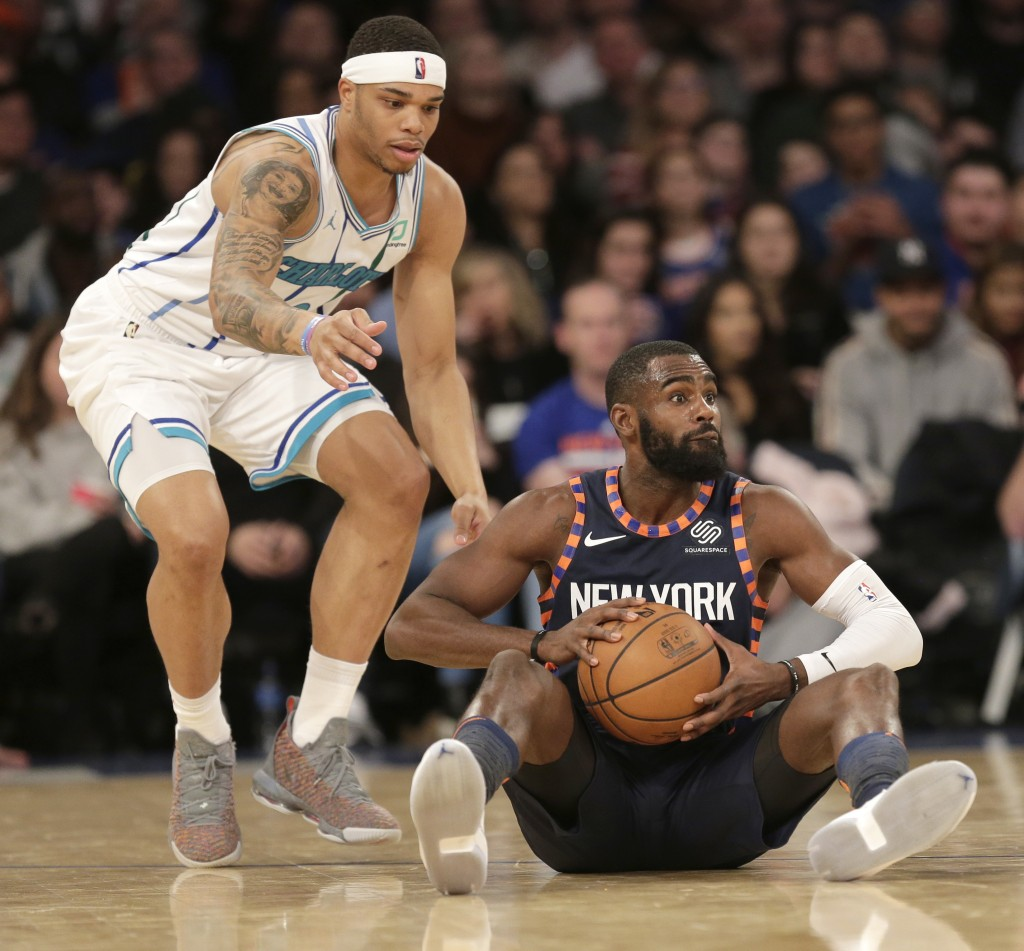New York Knicks' Tim Hardaway Jr., right, looks to pass while Charlotte Hornets' Miles Bridges defends during the second half of the NBA basketball ga...