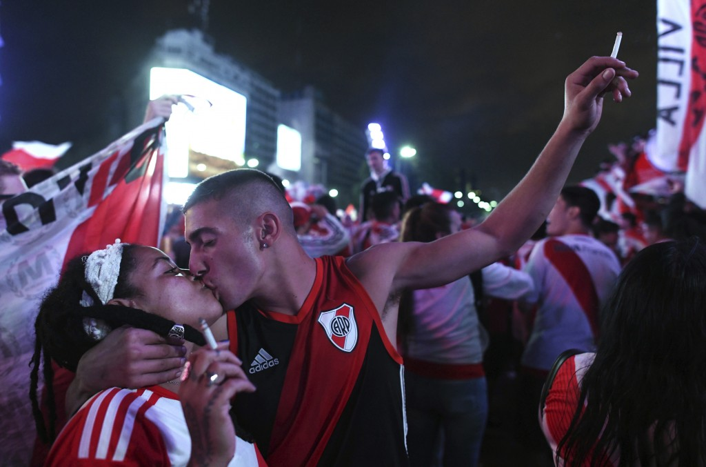 River Plate soccer fans kiss as they celebrate their team's 3-1 victory over Boca Juniors and clenching the Copa Libertadores championship title, at t