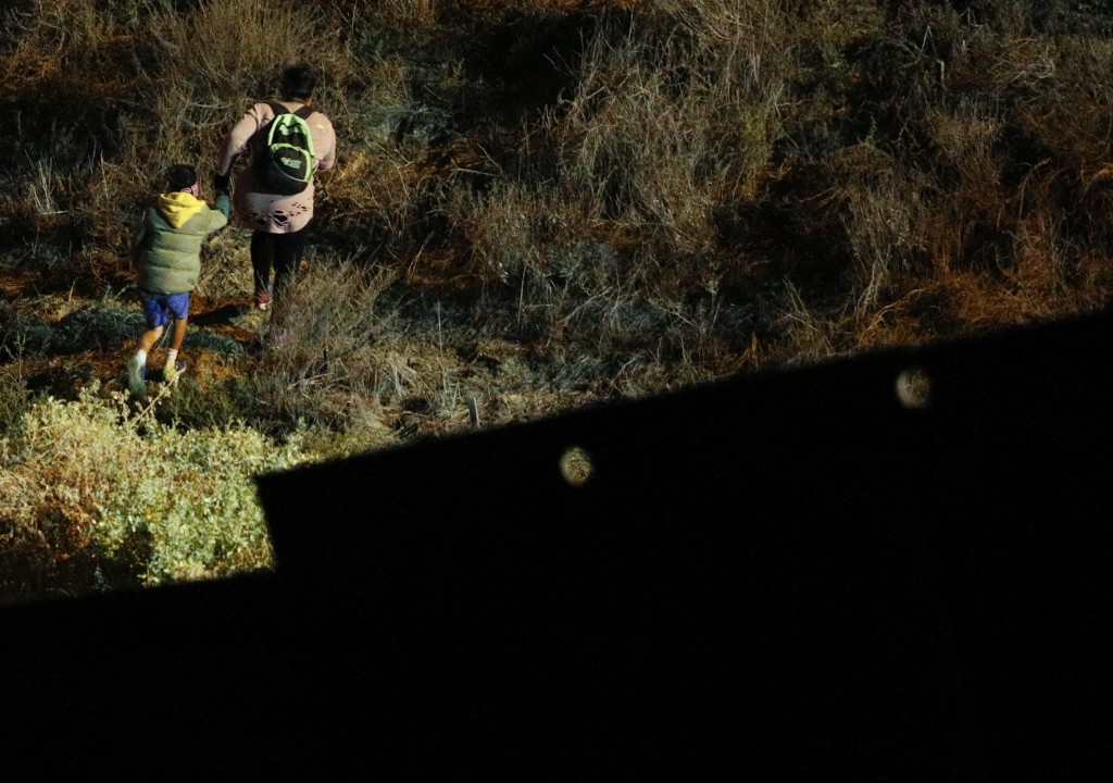 A woman and child migrant start up a hill in San Ysidro, California after climbing over the U.S. border wall from Playas de Tijuana, Mexico, where man
