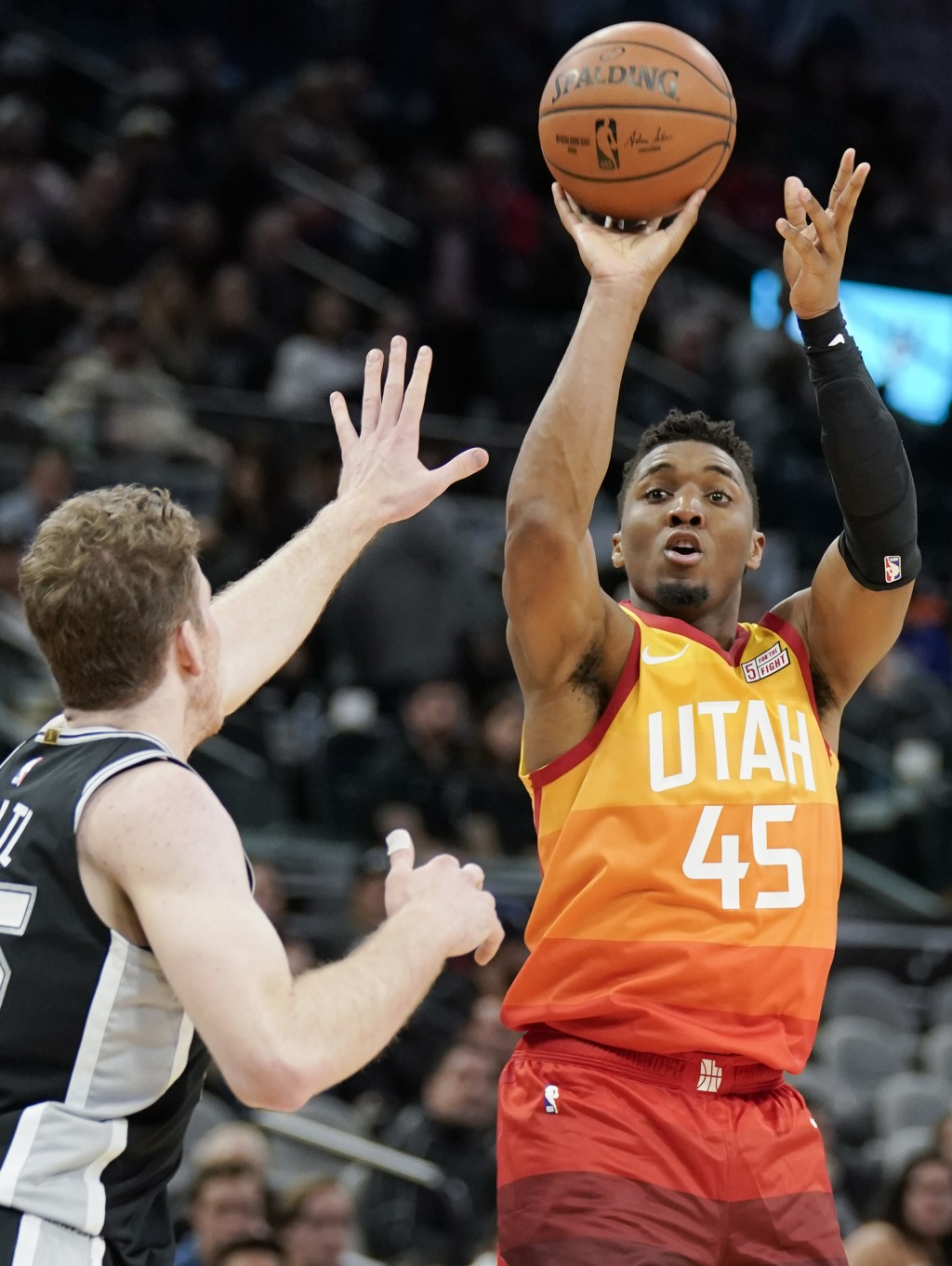 Utah Jazz guard Donovan Mitchell (45) shoots against San Antonio Spurs center Jakob Poeltl during the second half of an NBA basketball game, Sunday, D...