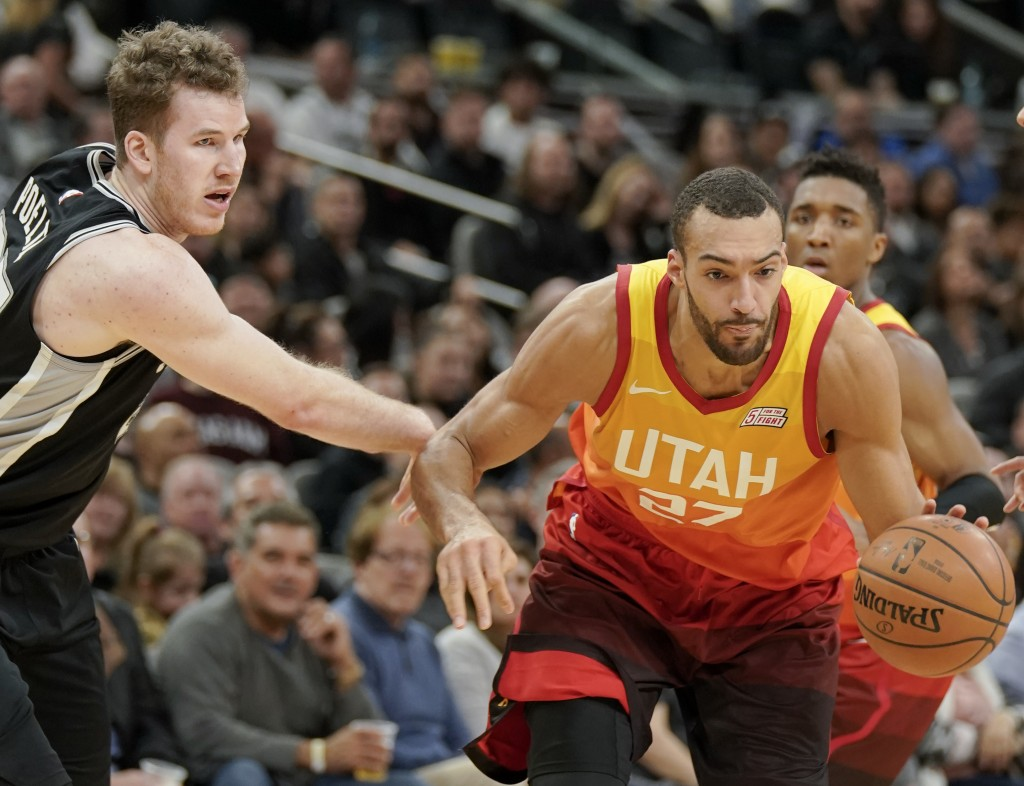 Utah Jazz center Rudy Gobert (27) drives around San Antonio Spurs center Jakob Poeltl during the second half of an NBA basketball game, Sunday, Dec. 9