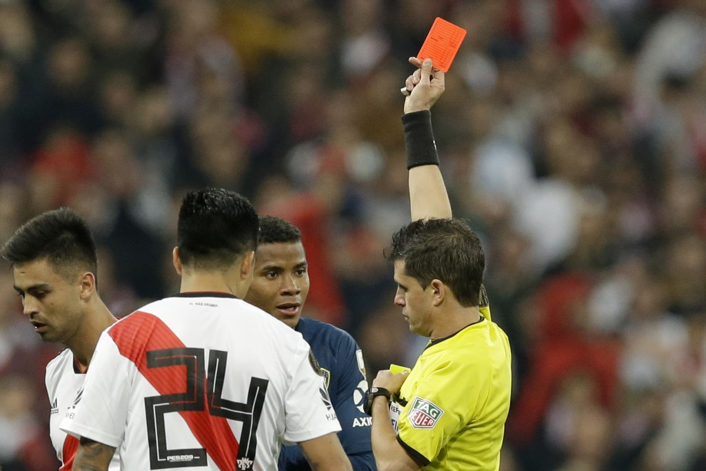 Referee Andres Cunha, of Uruguay, shows a red card to Wilmar Barrios of Argentina's Boca Juniors, center in blue, during a Copa Libertadores final soc