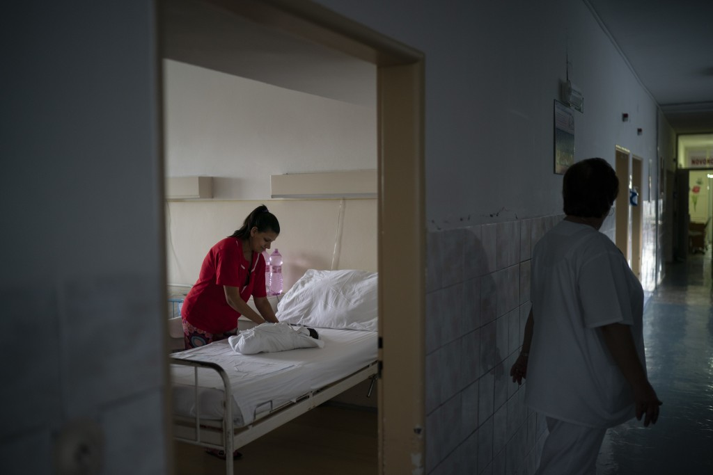 In this Nov. 15, 2018, photo, a nurse stands outside the room as Paulina Balazova prepares the clothes of her newborn baby at a hospital in Trebisov, ...