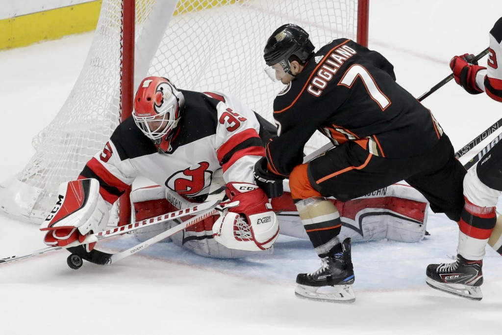 New Jersey Devils goaltender Cory Schneider, left, blocks a shot by Anaheim Ducks left wing Andrew Cogliano during the second period of an NHL hockey
