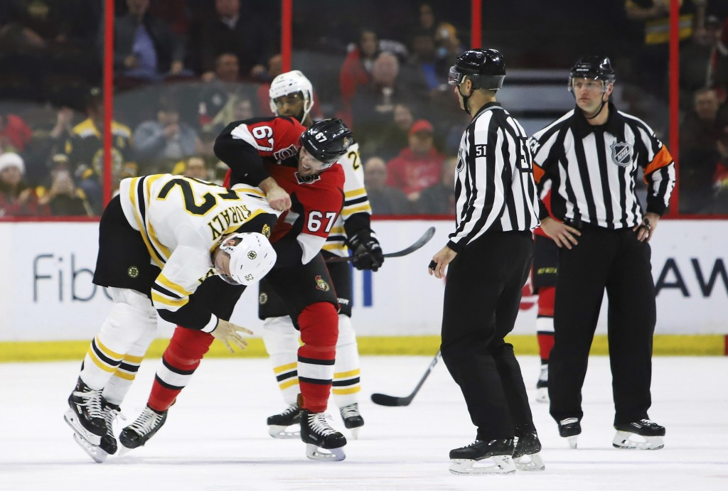 Boston Bruins centre Sean Kuraly (52) gets taken to the ice by Ottawa Senators defenseman Ben Harpur (67)during second period NHL hockey action in Ott...