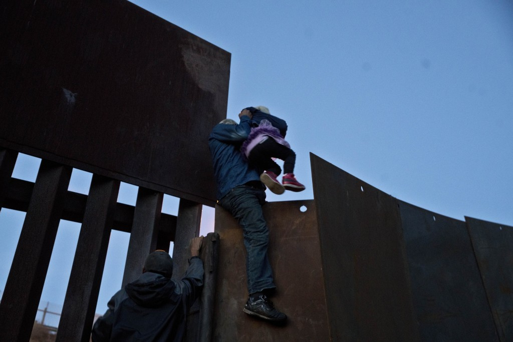 A Honduran migrant helps a young girl cross to the American side of the border wall, in Tijuana, Mexico, Sunday, Dec. 2, 2018. In November, President