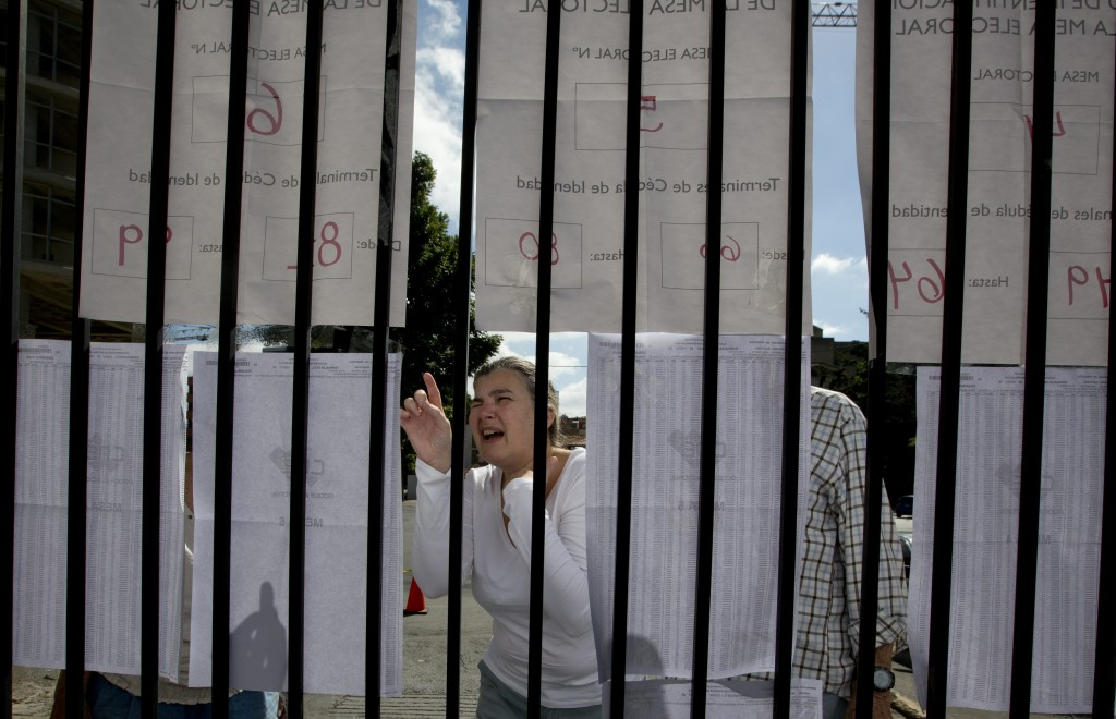 A voter looks for her voting station on a list outside of a polling station in Caracas, Venezuela, Sunday, Dec. 9, 2018. Venezuelans head to the polls...