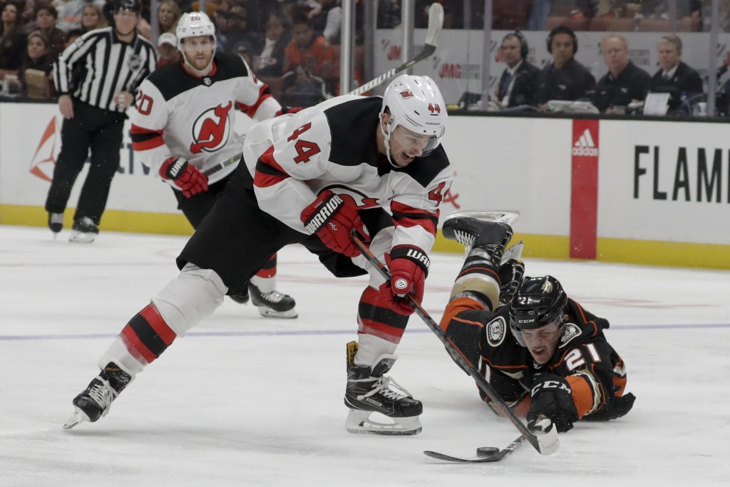 Anaheim Ducks defenseman Jake Dotchin, right, vies for the puck against New Jersey Devils left wing Miles Wood during the first period of an NHL hocke