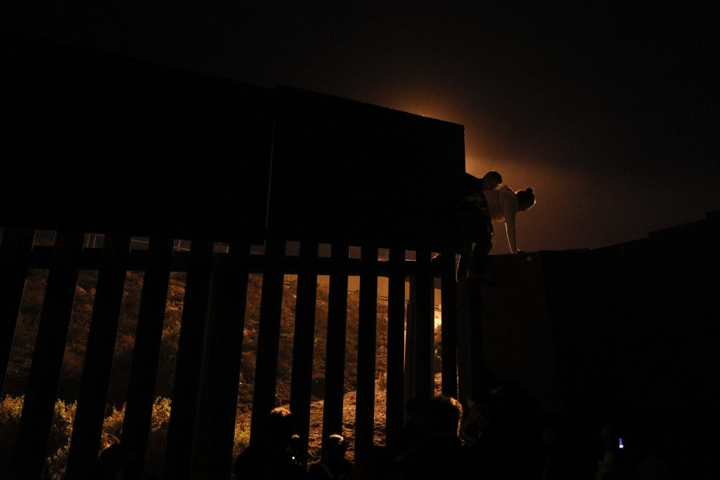 In a photo taken from Playas of Tijuana, Mexico, Honduran migrants climb over a section of the U.S. border fence before handing themselves in to borde