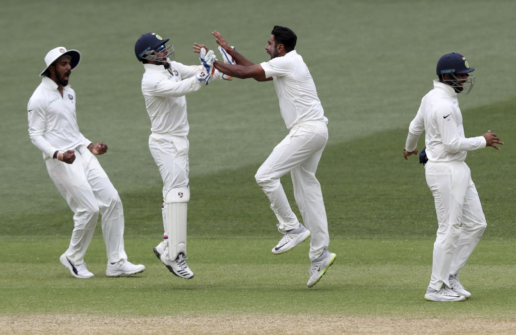 India's Ravi Ashwin, second right, celebrates with teammate Rishabh Pant after taking the wicket of Australia's Josh Hazlewood for India to win the fi...