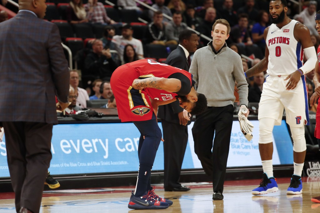 New Orleans Pelicans forward Anthony Davis, center, reacts after being injured in the first half of an NBA basketball game against the Detroit Pistons...