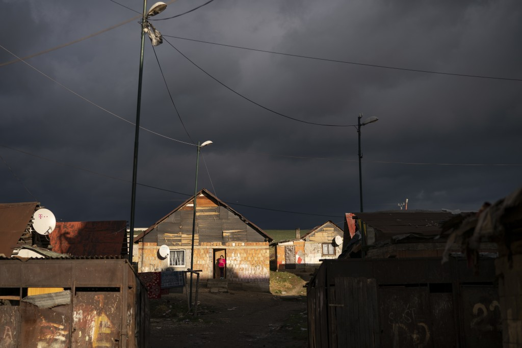 In this Nov. 14, 2018, photo, a Roma woman stands at the entrance of her house as dark clouds hover over the Podhorany village near Kezmarok, Slovakia...