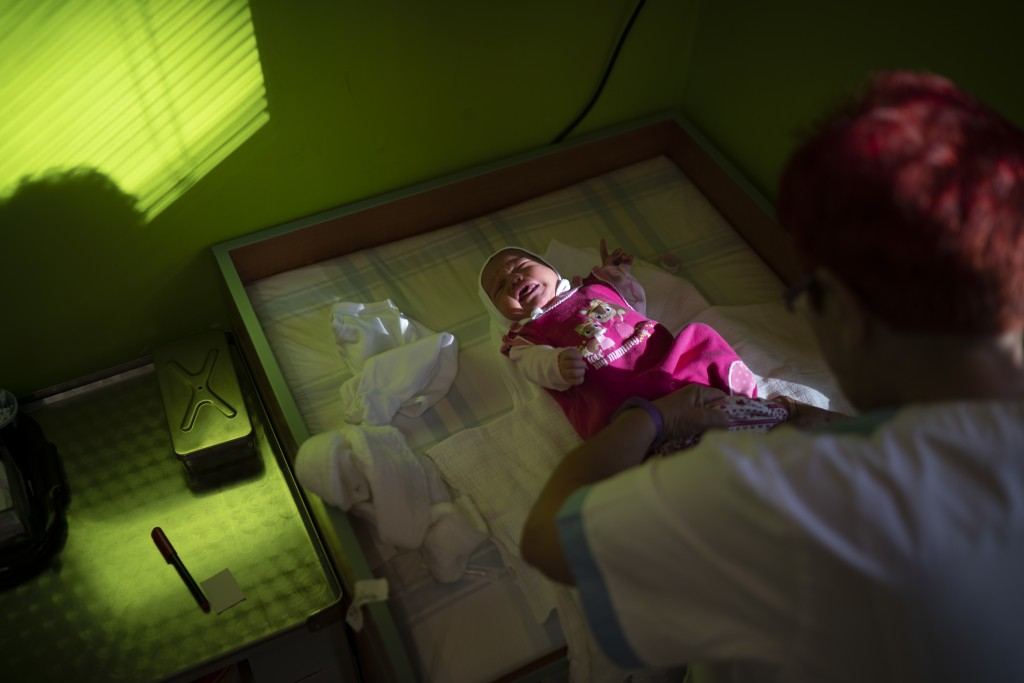 In this Nov. 16, 2018, photo, a nurse dresses a baby at the Kezmarok hospital in Kezmarok, Slovakia. An investigation by The Associated Press has foun
