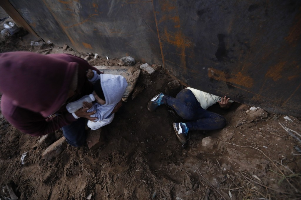 Honduran migrant Joel Mendez, 22, feeds his eight-month-old son Daniel as his partner Yesenia Martinez, 24, crawls through a hole under the U.S. borde