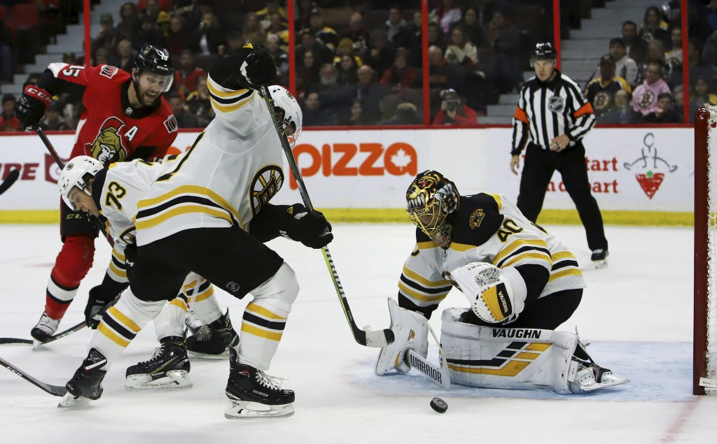 Boston Bruins goaltender Tuukka Rask (40) looks to scoop up a loose puck in front of the net during second period NHL hockey action against the Ottawa