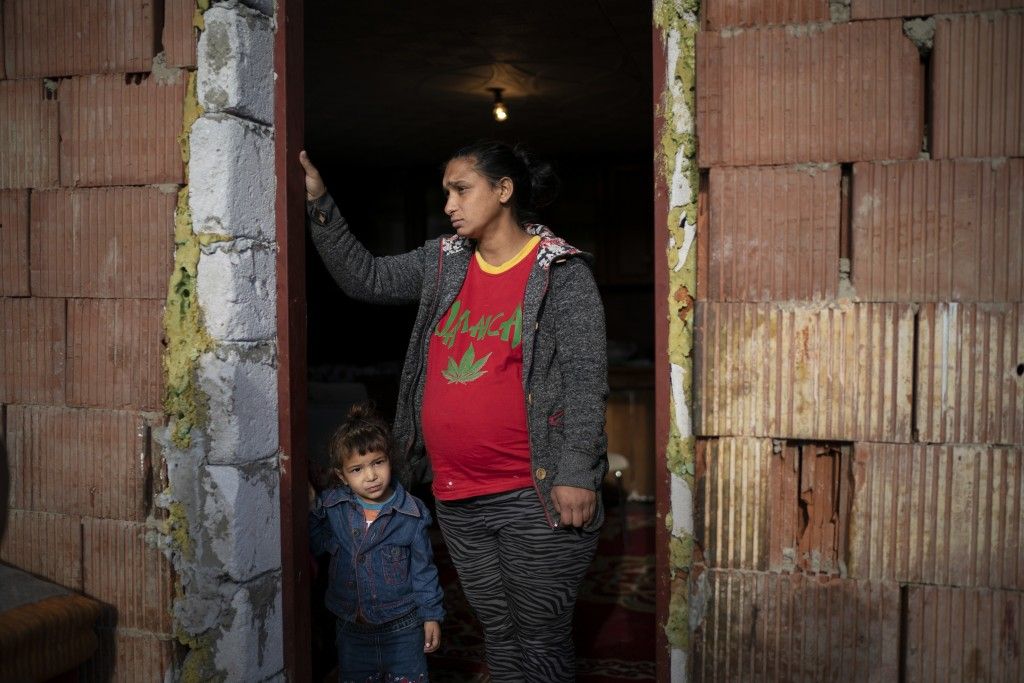 In this Nov. 14, 2018, photo, Jarmila Noskova, 33, stands at the entrance of her house with her daughter in Podhorany village near Kezmarok, Slovakia....